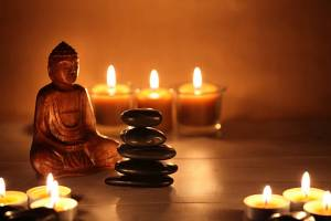 Zen stones balancing with candles and a Buddha figure